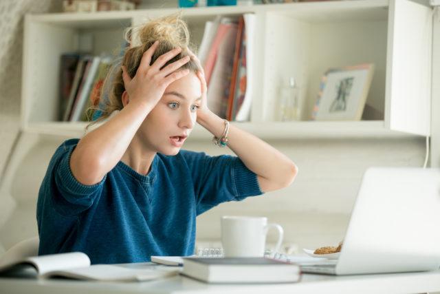 パソコン前でショックを受ける女性