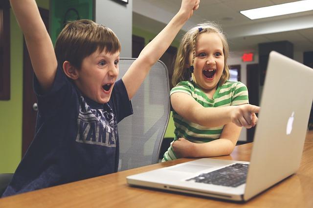 パソコン前で喜ぶ子供二人