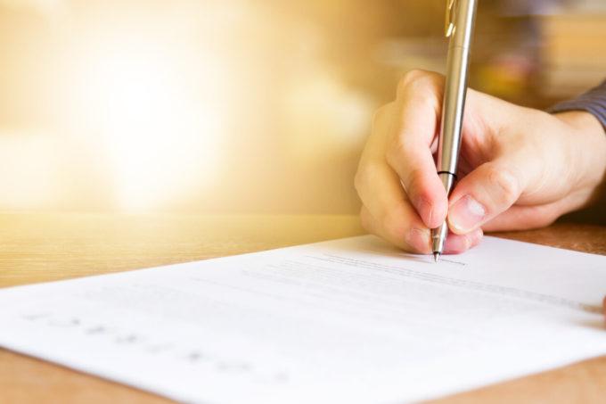 右手でペンを持ち手紙を書いてる
