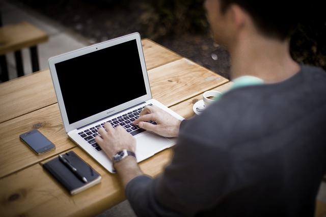 ノートパソコンと男性の後ろ姿