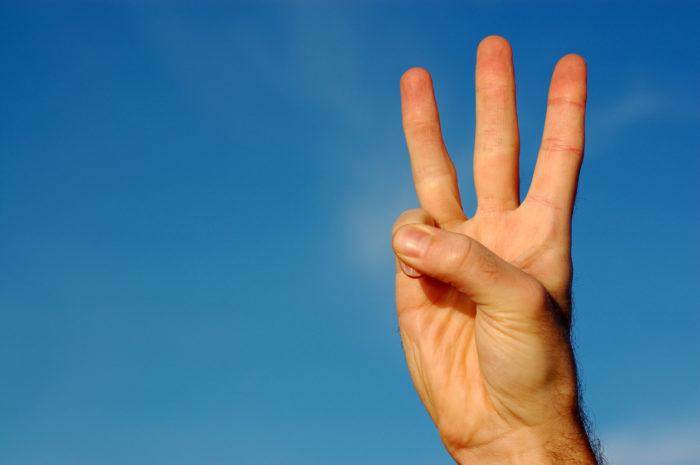 右手で3本の指を立てる