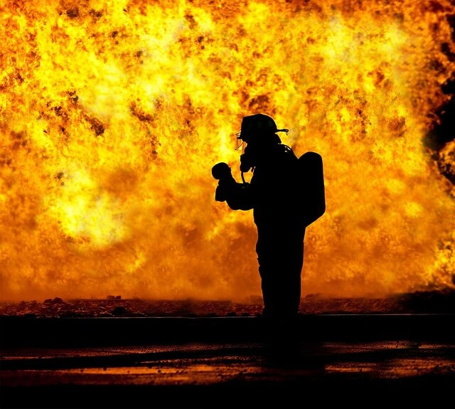 炎上する場所に消防士の影