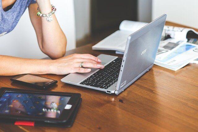 机の上でパソコンをする女性の右手